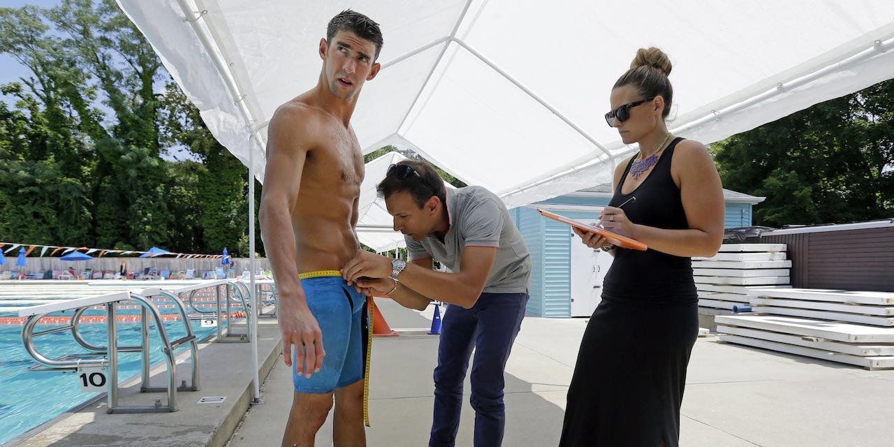 Michael Phelps, left, is measured in a prototype swimsuit before a training session. After partnering with Speedo through most of his swimming career, Phelps has agreed to a new deal with Aqua Sphere.