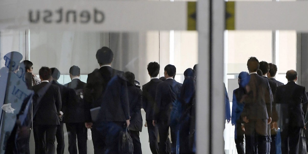 Investigators from the Health, Labor and Welfare Ministry enter the headquarters of Japan's top advertising agency Dentsu in Tokyo Monday.